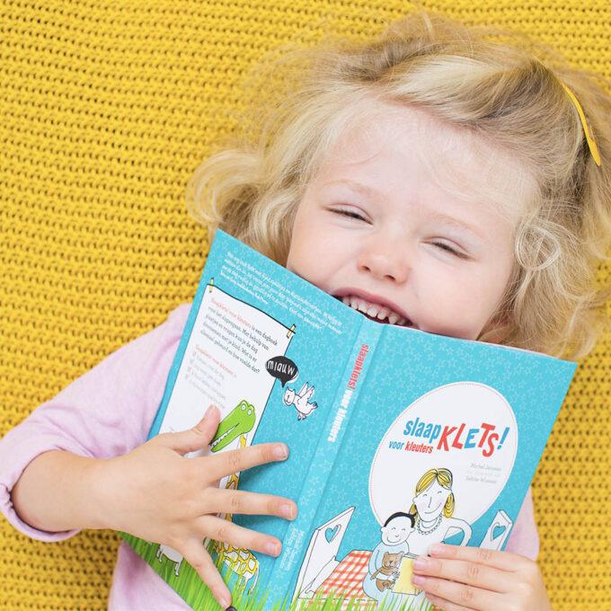 Kleuter met kinderboek Slaapklets Voor kleuters. EmotieBoeken.